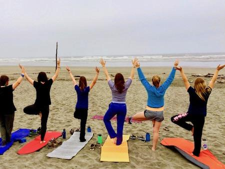 Girl's summer camp with yoga tree pose beach